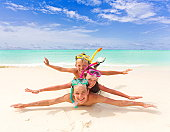 Three happy children with snorkels pretending to swim on sandy tropical beach, sea and blue sky background.