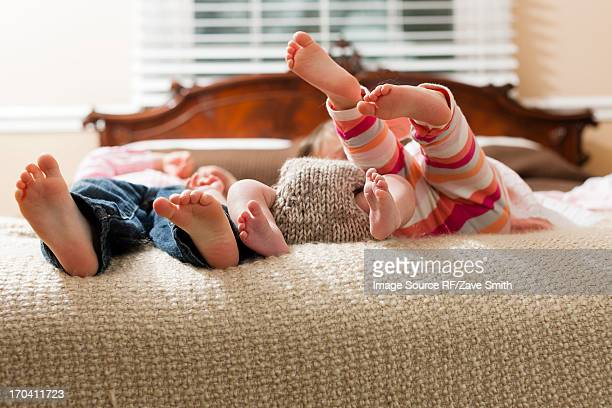Children laying with infant on bed