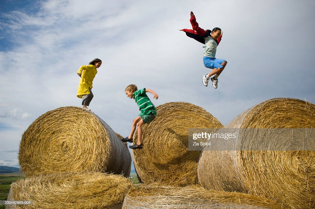 Children (7-13) leaping across bales of hay, side view : Stock Photo