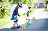 Children learning to roller skate on the road with cones. Twin girls are practising safe roller skating on a home driveway road wearing protective gear - helmets, knee, elbow and hand protectors or pa