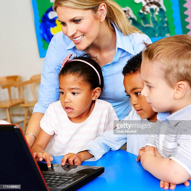 Children learning to use computer in classroom