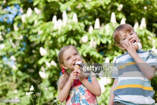 Children licking ice cream outdoors : Stock Photo