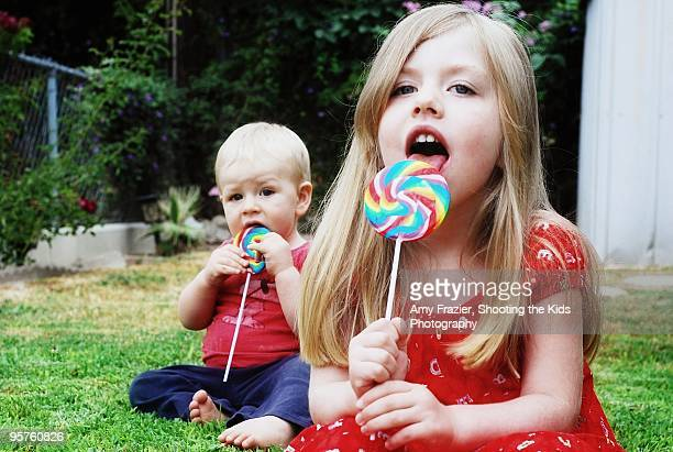 Children licking lollipops outside