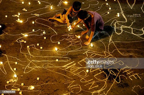 Children light candles during a vigil to commemorate the second anniversary of the Maguindanao massacre near the Malacanang palace in Manila on...