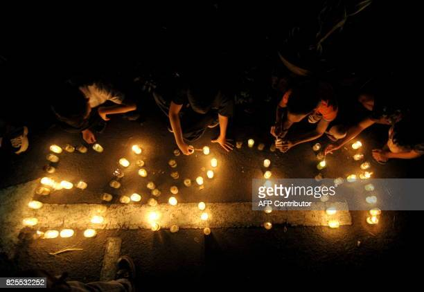 Children light candles during Earth Hour in Manila on March 26 2011 Australia's Opera House was the first of many global landmarks to go dark as...