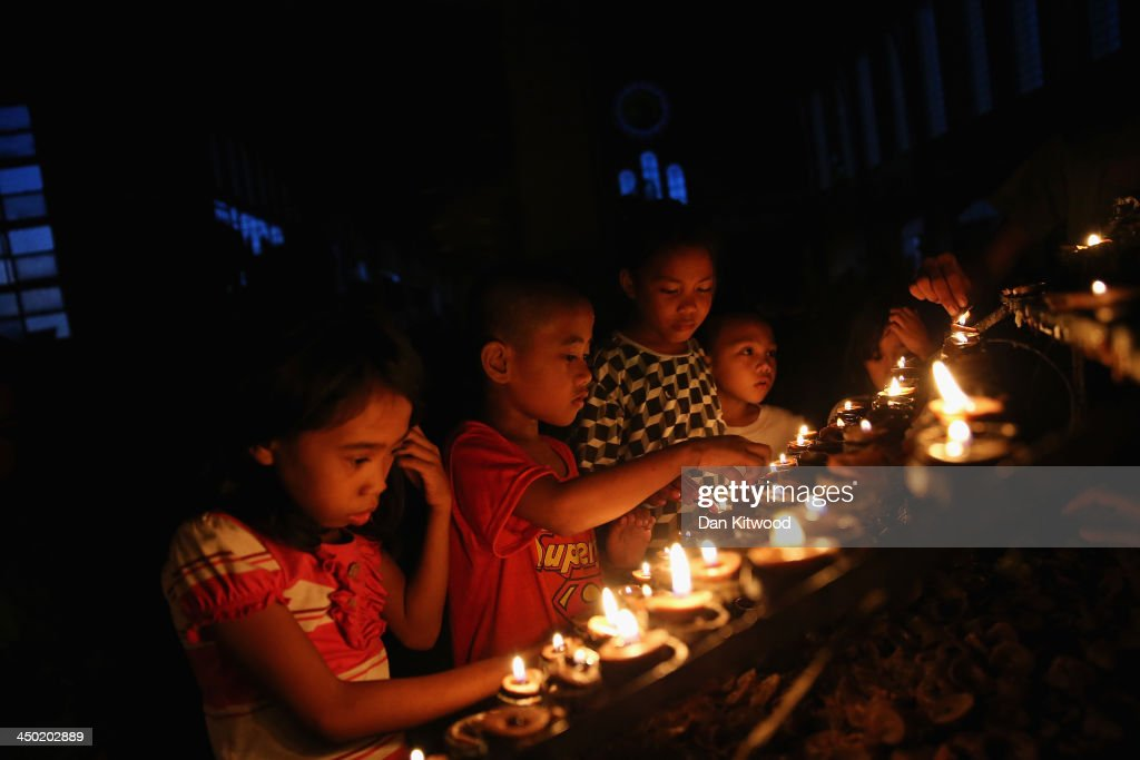 Children light candles in the Cathedral of Our Lord's Transfiguration Parish Palo church which has been converted into a shelter for displaced people...