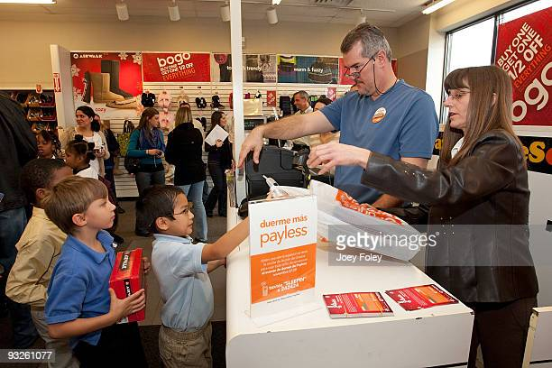Children lineup to give the cashier the coupons for their new shoes at Payless ShoeSource on November 20 2009 in Cincinnati Ohio