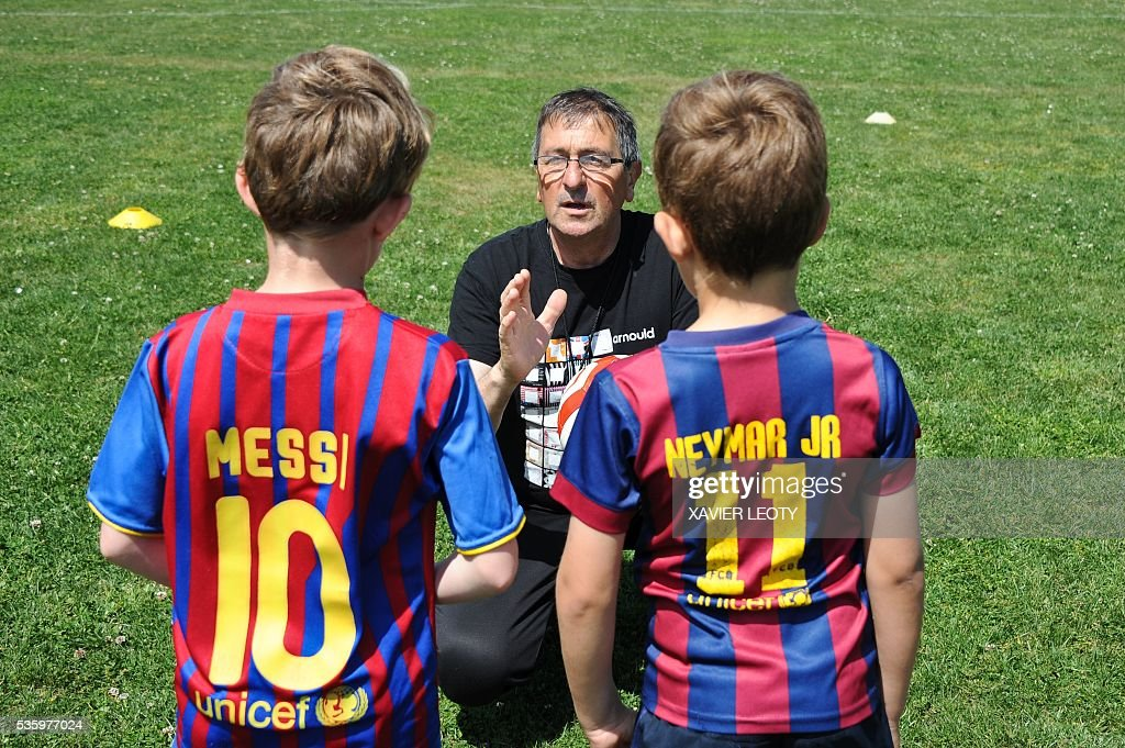 Children listen to a sports educator during a football training on May 25, 2016 in Saint-Martin-de-Ré, on the Re Island, western France. The national football team of Spain will have its base camp on the island for the upcoming Euro 2016 European football championships. / AFP / XAVIER