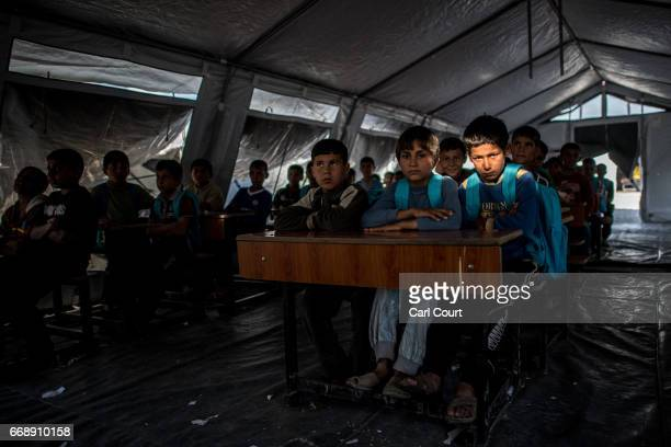 Children listen to a teacher as they sit in class at a school in Khazir refugee camp on April 15 2017 near Mosul Iraq Khazir camp with a capacity of...