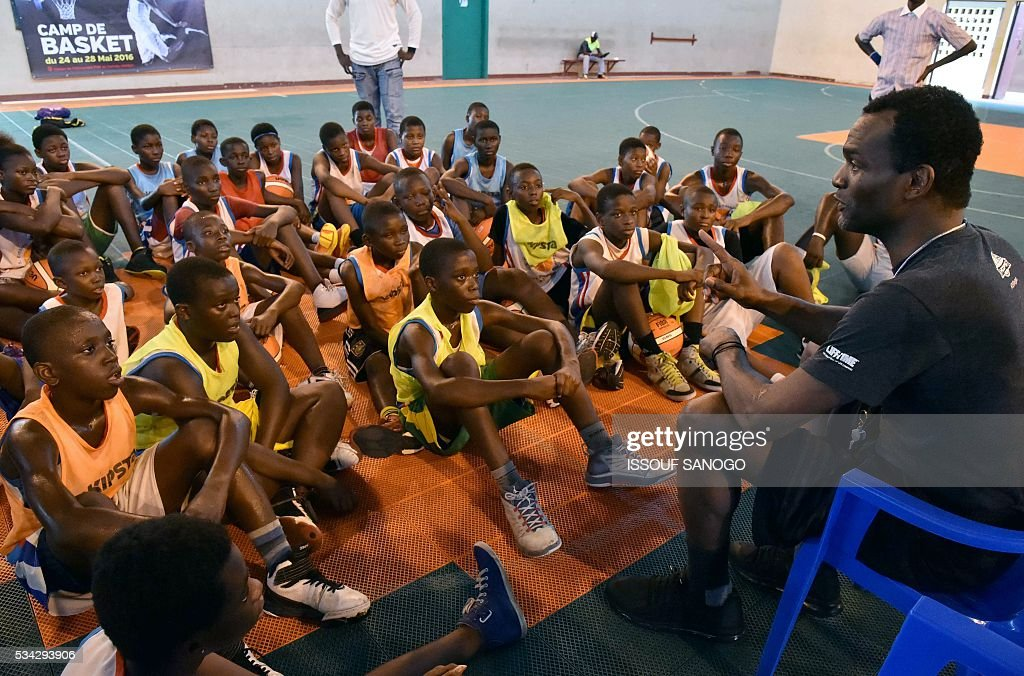 Children listen to American player Tommy Davis after a basketball match during the four days of workshop organised by the US embassy at the Felix Houphouet-Boigny University in Abidjan on May 25, 2016. / AFP / ISSOUF