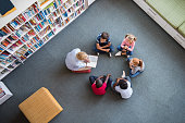 Teacher reading fairy tales to children sitting in a circle at library. Top view of librarian sitting with five multiethnic children on floor. Teacher reading book to cute girls and young boys at scho