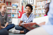 Multiethnic group of kids sitting on floor in circle around the teacher and listening a story. Discussion group of multiethnic children in library talking to woman. Portrait of smiling hispanic boy in