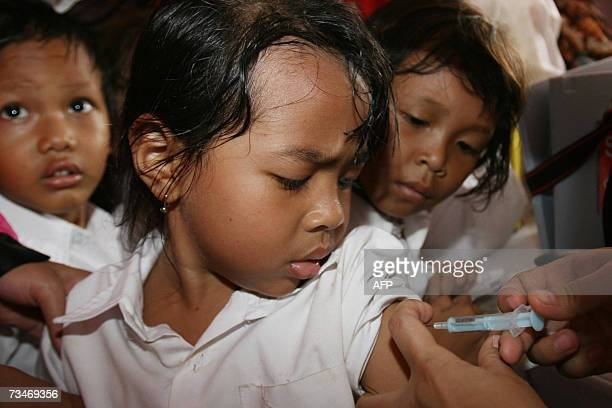 Children look as a young girl gets vaccinated in Jakarta 27 February 2007 IndonesiaIndonesia has launched a campaign to vaccinate 14 million children...