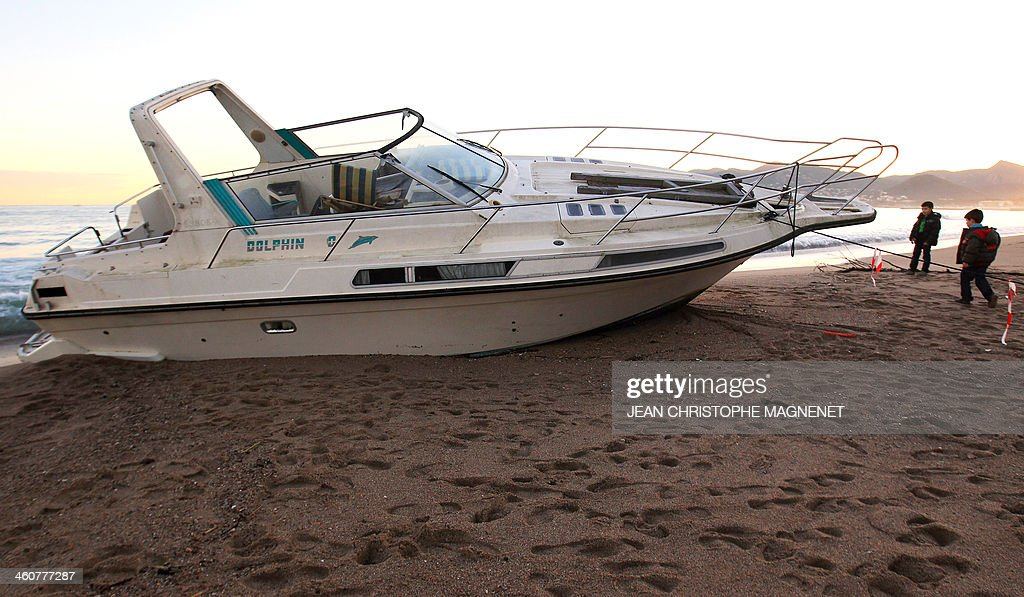 Children look at a boat on January 5, 2014 which washed ashore on a beach in Cannes, southeastern France, after the area was hit by gale-force winds and pounding rain.