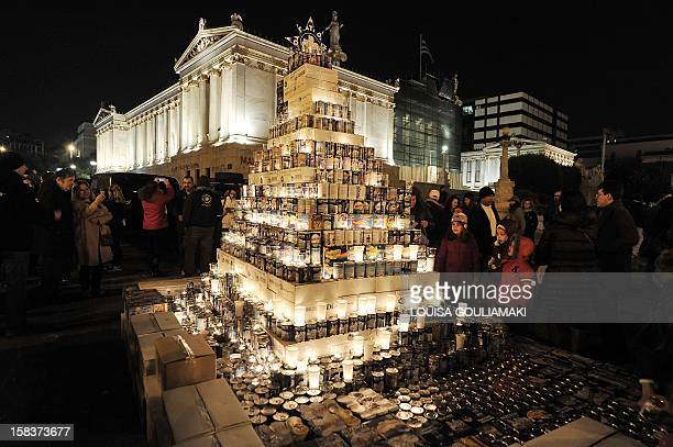 Children look at a Christmas tree made of milk tin cans after donating some on December 14 during an event organized by Medecins du Monde a...