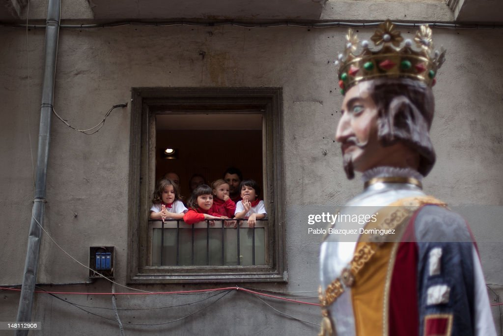 Children look at a Giant from a window during the Comparsa de gigantes y cabezudos (Parade of the giants and the big heads) on the fourth day of the San Fermin running-of-the-bulls on July 10, 2012 in Pamplona, Spain. Pamplona's famous Fiesta de San Fermin, which involves the running of the bulls through the historic heart of Pamplona for eight days starting July 7th, was made famous by the 1926 novel of U.S. writer Ernest Hemmingway called 'The Sun Also Rises.'