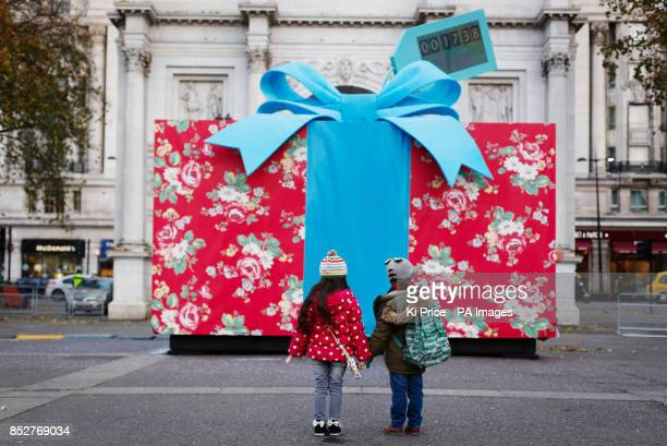 Children look at a giant present containing taxis covered in Cath Kidston prints which will offer free journeys to the Cath Kidston flagship store on...