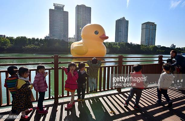Children look at a giant yellow rubber duck floating on Seokchon Lake in Seoul on October 14 2014 The 16meter high rubber duck an installation by...