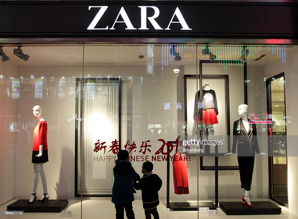 Children look at a window display outside a Zara store, operated by Inditex SA, at night in the East Nanjing Road shopping area of Shanghai, China, on Friday, Feb. 1, 2013. China's services industries grew at the fastest pace since August as gains in retailing and construction aid government efforts to drive a recovery in the world's second-biggest economy. Photographer: Tomohiro Ohsumi/Bloomberg via Getty Images