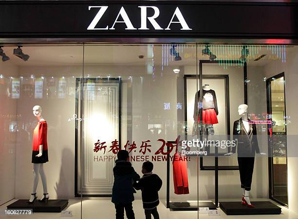 Children look at a window display outside a Zara store operated by Inditex SA at night in the East Nanjing Road shopping area of Shanghai China on...