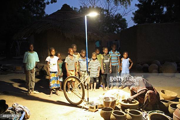 Children look at a woman making 'canari' a small spherical jar under a mobile solarpowered streetlamp named by locals as 'Foroba Yelen' in the...