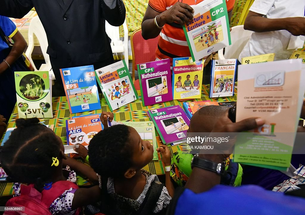 Children look at books displayed during the International Book Fair of Abidjan on May 28, 2016. / AFP / Sia KAMBOU
