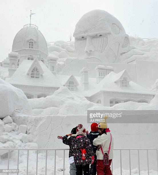 Children look at the 15metretall snow statue of 'Attack on Titan' during the first day of the 67th Sapporo Snow Festival in Sapporo Hokkaido on...