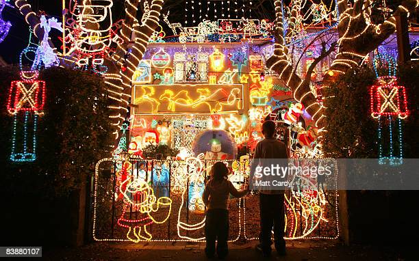 Children look at the Christmas lights displayed on a house on December 1 2008 in Melksham England The householder Alex Goodwind who says he does it...
