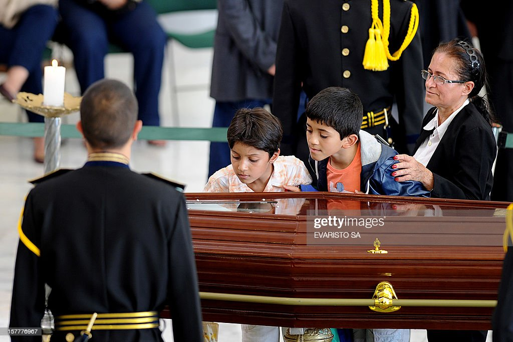 Children look at the coffin of Brazilian architect Oscar Niemeyer during his funeral at Planalto Palace, in Brasilia, on December 6, 2012. Niemeyer, the Brazilian icon who revolutionized modern architecture and designed much of the country's futuristic capital Brasilia, died in Rio de Janeiro Wednesday at 104. The body will return to Rio de Janeiro for another funeral wake followed by the burial, according to Rio de Janeiro's Mayor Eduardo Paes. AFP PHOTO/Evaristo SA