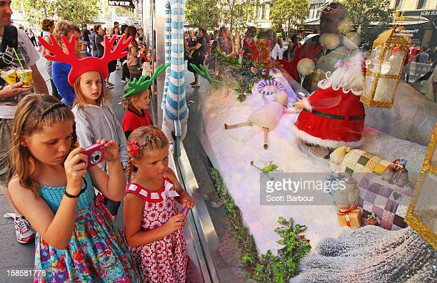 Children look at the Myer Christmas window display on December 20 2012 in Melbourne Australia Australian retailers are looking forward to an improved...