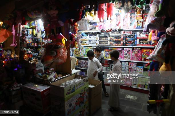 Children look at toys at a shop in the popular Souq Waqif market in the Qatari capital Doha on June 7 2017 Saudi Arabia Egypt the UAE and Bahrain...