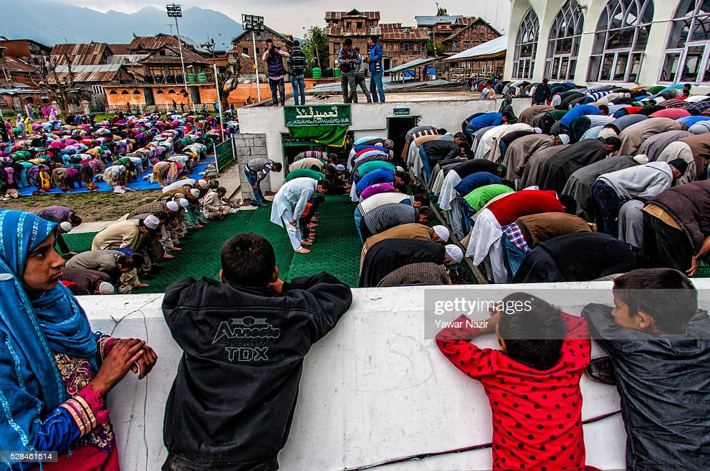 Children look on as Kashmiri Muslims pray outside the Hazratbal Shrine on the MehrajuAlam which marks ascension day the journey from earth to heaves...