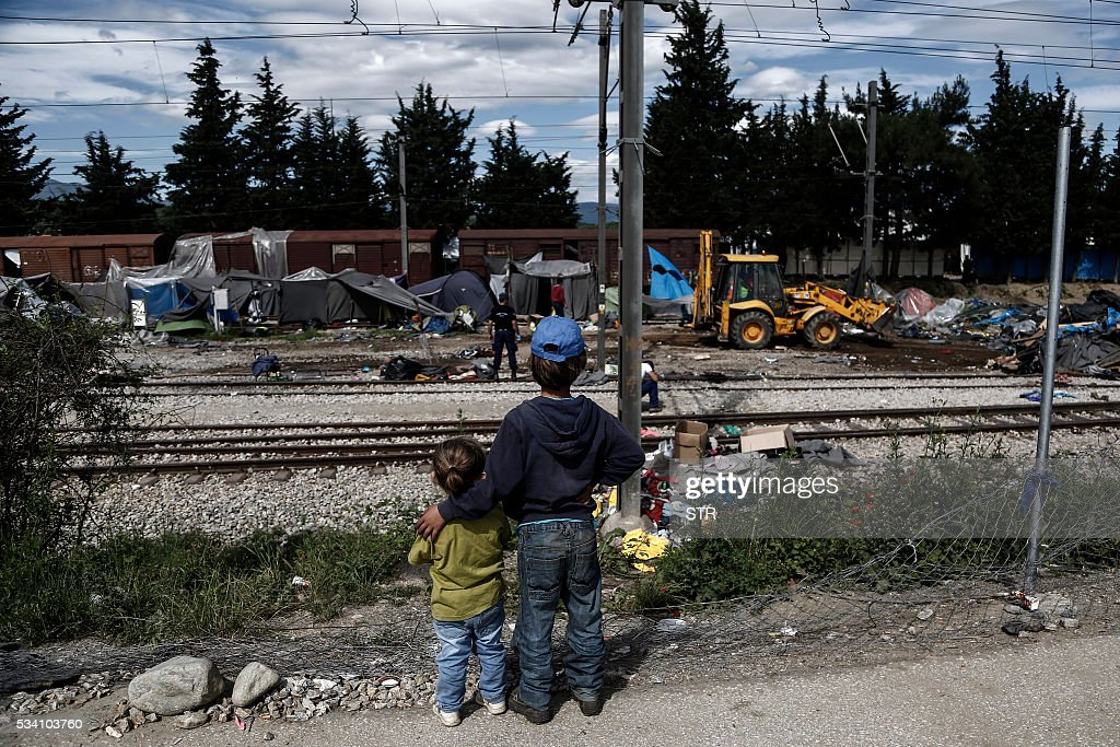 Children look on as police officers remove tents during a police operation at a refugee camp at the border between Greece and Former Yugoslav Republic of Macedonia (FYROM), near the village of Idomeni, northern Greece on May 25, 2016. Greek police restarted an operation to move migrants out of Idomeni, the squalid tent city where thousands fleeing war and poverty have lived for months. The migrants and refugees were bussed to newly opened camps near Greece's second city Thessaloniki, about 80 kilometres (50 miles) to the south. / AFP / POOL / STR