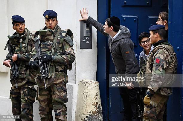 Children look out from a doorway as armed soldiers patrol outside a School in the Jewish quarter of the Marais district on January 13 2015 in Paris...