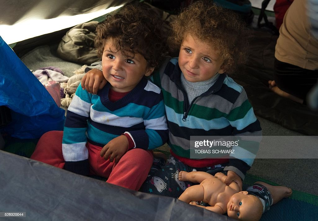 Children look out of a tent at a makeshift camp for migrants and refugees near the village of Idomeni, not far from the Greek-Macedonian border, on April 30, 2016. Some 54,000 people, many of them fleeing the war in Syria, have been stranded on Greek territory since the closure of the migrant route through the Balkans in February. / AFP / TOBIAS