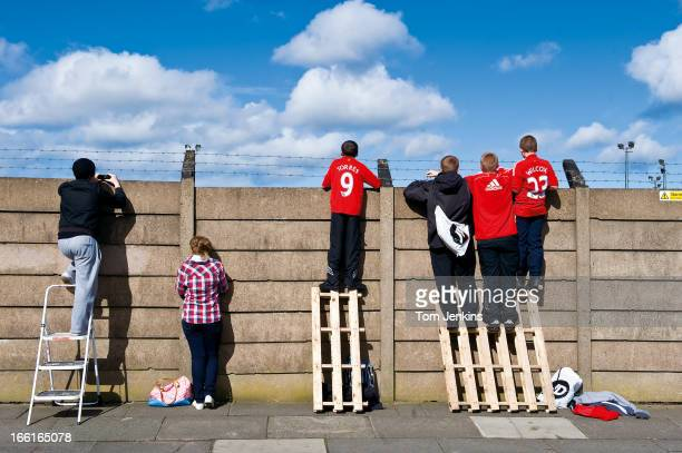 Children look over a fence to watch Liverpool FC training at the Melwood training centre on April 6th 2009 in Liverpool An image from the book 'In...