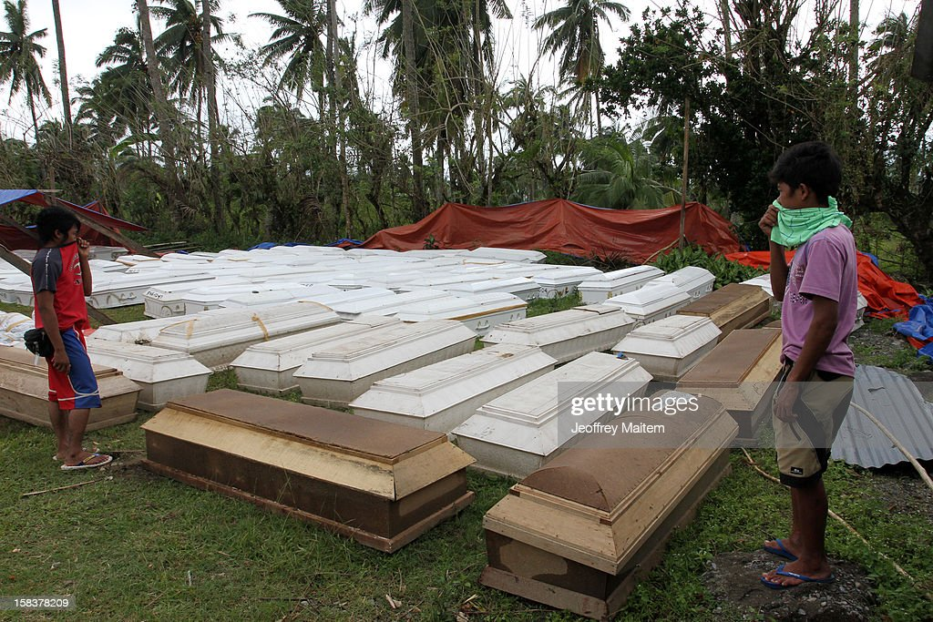 Children look over coffins with the dead December 14, 2012 in the devastated town of New Bataan, Compostela Valley province, the Philippines. More than 900 people were killed and nearly a thousand remain missing after Typhoon Bopha, the strongest storm to hit the Philippines this year, pounded the region.