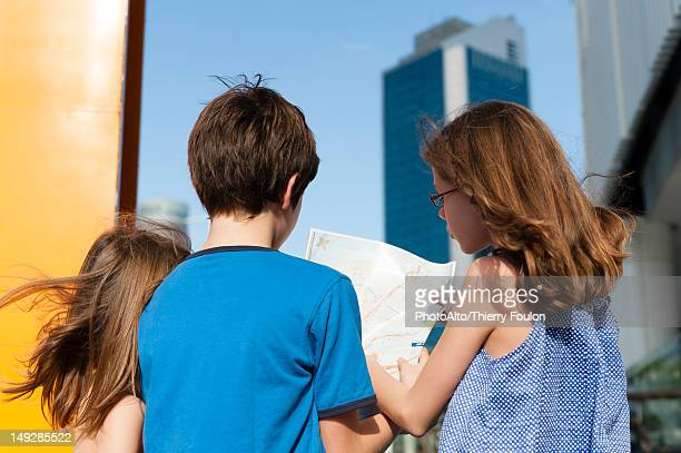 Children looking at map while sightseeing in city