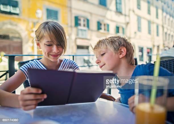 Children looking at the menu in Pisa street restaurant