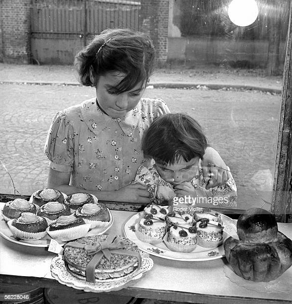 Children looking at the shop window of a cake shop France on 1950's Bouvet303
