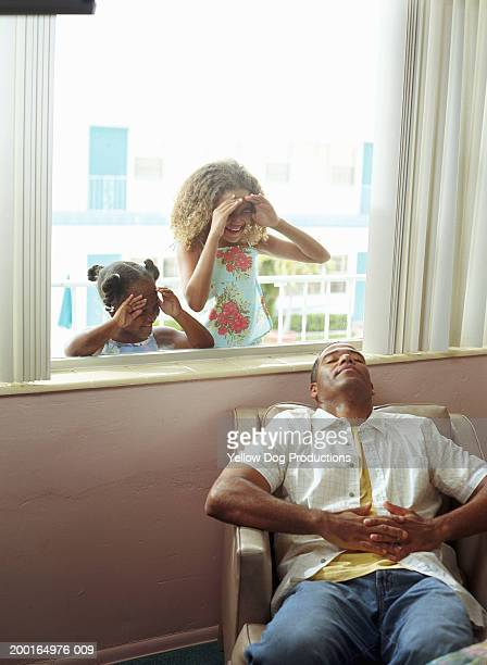 Children (5-10) looking in hotel window, father sleeping on chair