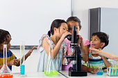 Schoolchildren looking in microscope in lab