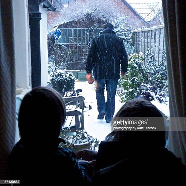 Children looking out of window at man in snow