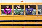 Children looking out school bus window
