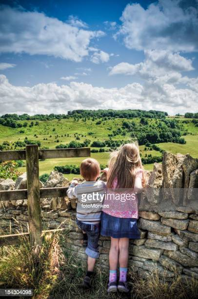 Children looking over country wall, HDR image, Cotswolds, Gloucestershire