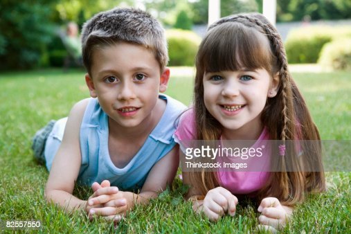 Children lying down in grass : Stock Photo