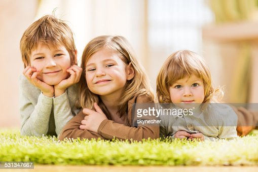 Children lying down on carpet.