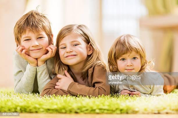 Bambini sdraiato sul tappeto.