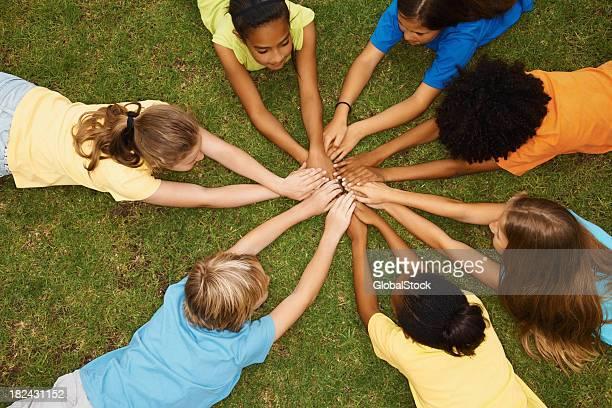 Enfants, allongé sur l'herbe avec leurs mains ensemble