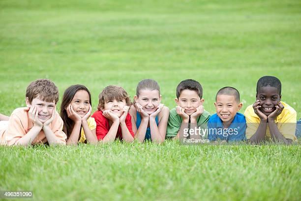 Kinder liegen in einer Reihe auf dem Rasen